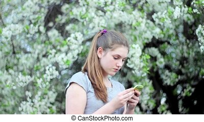 Teen girl with smartphone in the park. Spring. Against the background of a flowering tree