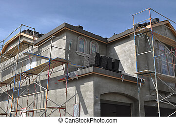 New Stucco Home Under Construction with Blue Sky Background
