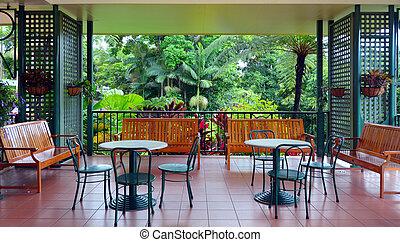 Colonial furnitures on a balcony against a tropical rain...