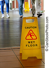 Warning sign for slippery floor with people legs in the...