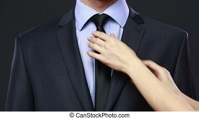 Woman fixing a mans tie girl gently straightens tie