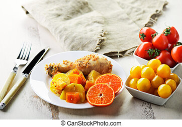 chicken drumstick cooked in spices with vegetables and citrus in the plate on the white wooden table. horizontal