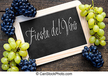 white and blue grapes with a slate on wooden table, spanish...
