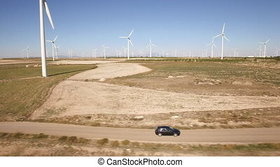 Following a black car in windmill farm - Aerial view of...