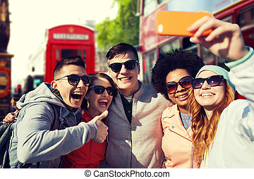 smiling friends taking selfie with smartphone - people,...