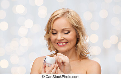happy woman with cream jar over holidays lights - beauty,...