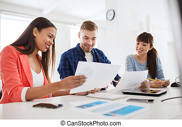happy creative team or students working at office -...