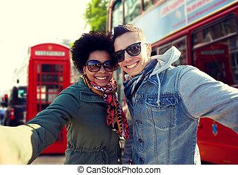 happy teenage couple taking selfie in london city - tourism,...