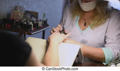 Manicurist treating customer at beauty salon nails close up