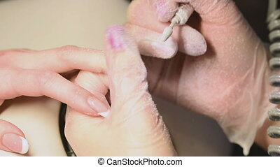 Manicurist treating customer at beauty salon. nails close up