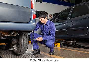 Technician Using Rim Wrench To Fix Car Tire - Young male...