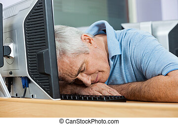 Senior Male Student Sleeping At Computer Desk