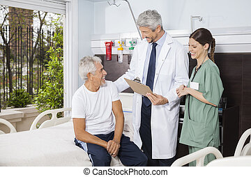 Doctor And Nurse Looking At Senior Patient At Rehab Center -...
