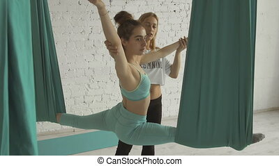 Yoga Choach Helps Female Student To Stretch Legs And Do...