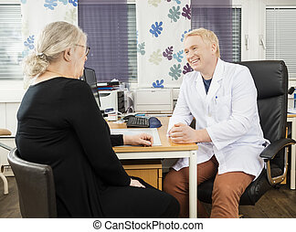 Happy Doctor Communicating With Senior Patient At Desk