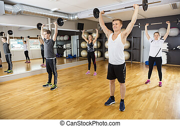 Men And Women Lifting Barbells In Fitness Club - Young men...