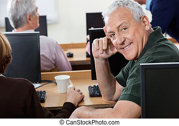 Portrait Of Happy Senior Man Sitting In Computer Class
