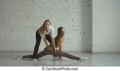 Yoga Trainer Helps Female Student To Stretch Legs And Do The...