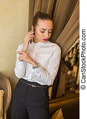 Portrait of young business woman talking on a cell phone -...
