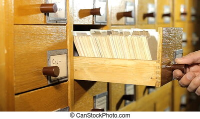 Man looking for a book in the library card catalog