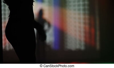 silhouettes of dancing people in night club