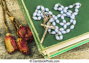 Rosary, bible and dried roses