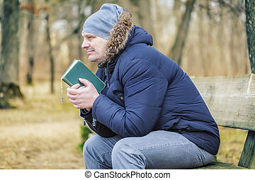Man with Bible and rosary on bench