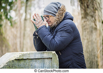 Man with Bible and Rosary praying