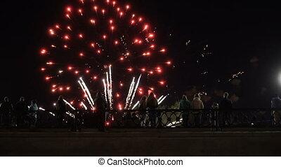 people standing on a bridge watching fireworks - People in...