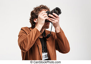 Man photographing something on camera - Man with curly hair...