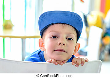 Handsome small boy in a blue baseball cap leaning his chin...