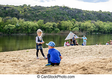 Brother and sister playing on sand near river - Little boy...