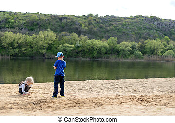 Boy and girl playing on sand near river - Little boy in hat...