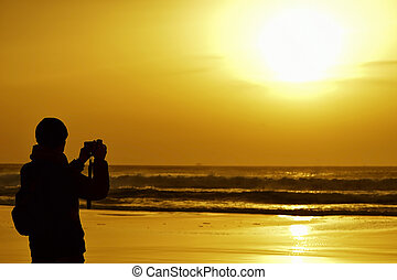 young man taking a picture in front of the sea at dusk - the...