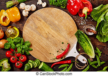 Cutting Board, Fresh Vegetables and Herbs on Table - High...