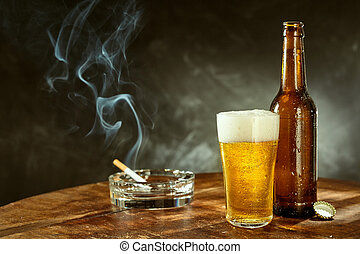 Burning cigarette and cold beer in a pub - Burning cigarette...