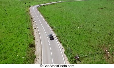 Car driving along a winding rural road through lush green...