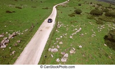 Lone car driving on a winding rural road through open...