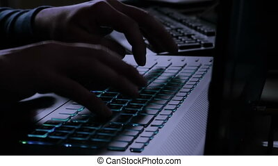 man typing on notebook keyboard with blue light tint, with...