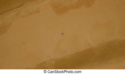 Birds eye view of woman laying in sand - Birds eye view of...
