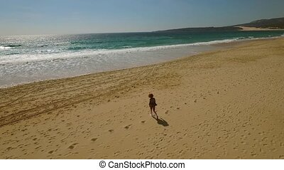 Woman walking long a deserted tropical beach at sunset...