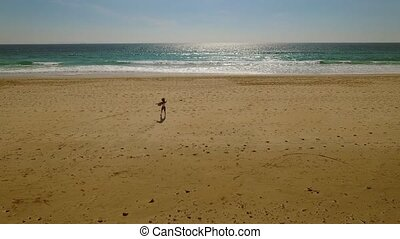 Lone young woman walking on a deserted beach in evening...