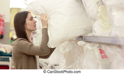 young woman chose a pillow in a supermarket - young woman...