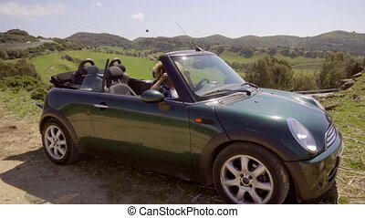 Young woman driving compact car in countryside - Young woman...