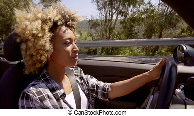 Attractive young African American woman driving her car...