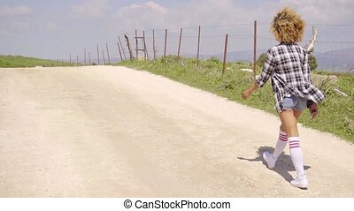 Young woman running along a rural dirt road - Trendy young...