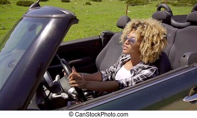 Trendy young woman driving a sports car on a rural road...