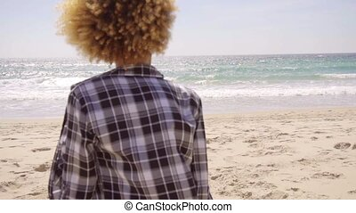 Afro-American Woman Walks Beach Along - Rear view of young...