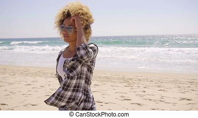 Young woman walking on a windy sandy beach