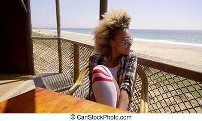 Young woman relaxing at a beachfront cafeteria sitting...